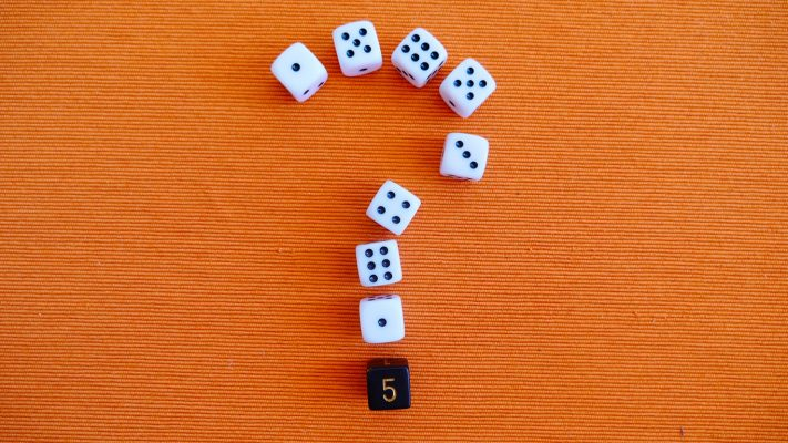Question mark made from dice on orange background